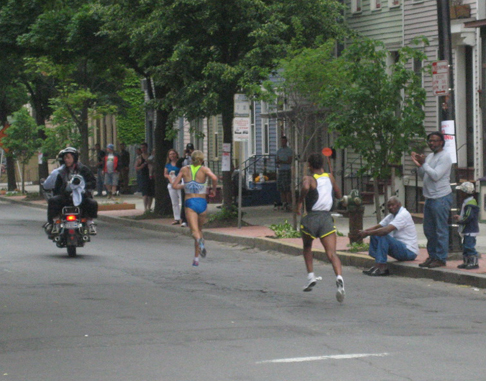 Note How The Runner In Front Is Trying To Pass The Motorcycle