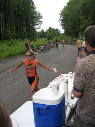 A Competitor Grabs Water At The Start Of The Run