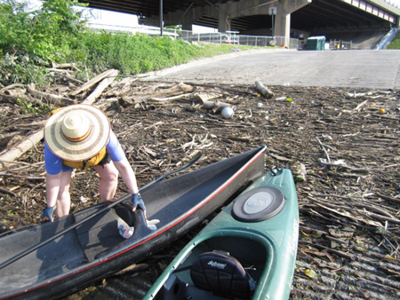 The Wife Complains Bitterly As She Hauls Her Canoe Across Accumulated Debris At The Albany Boat Launch