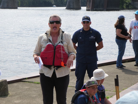 An Event Organizer Hollers Safety Instructions While The Coast Guard Heavy Stands Behind Her